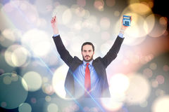 Composite image of businessman holding up reading glasses and calculator Royalty Free Stock Photo