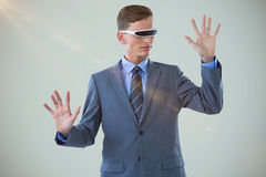 Composite image of businessman imagining while using virtual reality glasses Royalty Free Stock Images