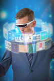 Composite image of businessman imagining while using virtual reality glasses 3d. Businessman imagining while using virtual reality glasses against blue Stock Images