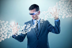 Composite image of businessman imagining while using virtual reality glasses 3d Royalty Free Stock Photos