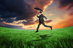 Composite image of businessman jumping holding an umbrella Royalty Free Stock Image