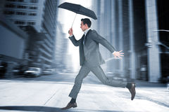Composite image of businessman jumping holding an umbrella Stock Photo