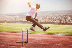 Composite image of businessman jumping a hurdle stock photography