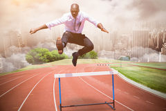Composite image of businessman jumping a hurdle royalty free stock images