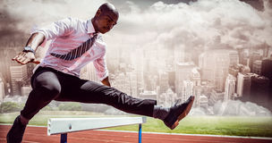 Composite image of businessman jumping a hurdle stock images