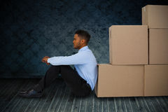 Composite image of businessman leaning on cardboard boxes against white background Royalty Free Stock Photos