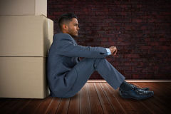 Composite image of businessman leaning on cardboard boxes against white background stock photos