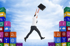 Composite image of businessman leaping with his briefcase Royalty Free Stock Photo