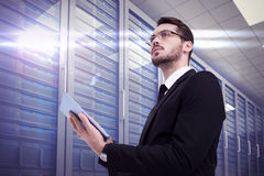 Composite image of businessman looking away while using tablet Stock Image