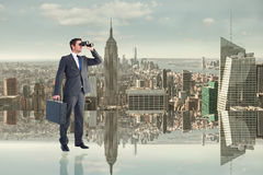 Composite image of businessman looking through binoculars Royalty Free Stock Images