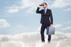 Composite image of businessman looking through binoculars holding briefcase Stock Photo