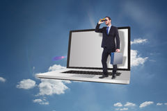 Composite image of businessman looking through binoculars holding briefcase Royalty Free Stock Image
