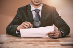 Composite image of businessman looking at document through magnifying glass stock images