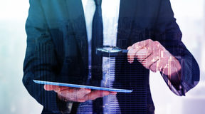 Composite image of businessman looking at his tablet through magnifying glass Stock Images
