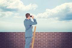 Composite image of businessman looking on a ladder Royalty Free Stock Photography