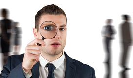 Composite image of businessman looking through magnifying glass Royalty Free Stock Photos