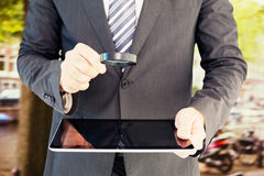 Composite image of businessman looking at tablet with magnifying glass Stock Images