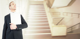 Composite image of businessman looking up holding laptop Royalty Free Stock Image