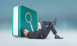 Composite image of businessman lying on the floor reading book Stock Image