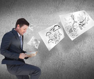 Composite image of businessman lying on the floor reading a book Royalty Free Stock Image