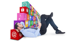Composite image of businessman lying on floor using tablet Stock Image