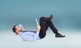 Composite image of businessman lying on floor using tablet Royalty Free Stock Image