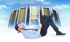 Composite image of businessman lying on floor using tablet Royalty Free Stock Photography