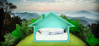 Composite image of businessman lying on sofa. Businessman lying on sofa against trees and mountain range against cloudy sky Royalty Free Stock Image