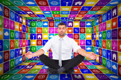 Composite image of businessman meditating in lotus pose Stock Images