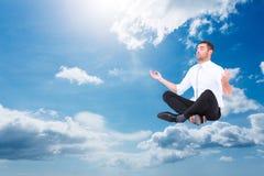 Composite image of businessman meditating in lotus pose Stock Photos