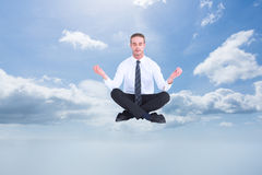 Composite image of businessman meditating in lotus pose Royalty Free Stock Photography