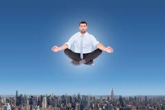 Composite image of businessman meditating in lotus pose Stock Photo