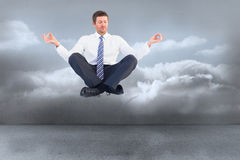 Composite image of businessman meditating in lotus pose Royalty Free Stock Images