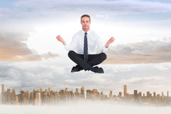 Composite image of businessman meditating in lotus pose Stock Image