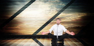 Composite image of businessman meditating in lotus pose Stock Photos