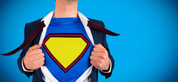 Composite image of businessman opening shirt in superhero style. Businessman opening shirt in superhero style against blue background with vignette royalty free stock images