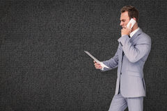 Composite image of businessman on the phone. Businessman on the phone against grey background Royalty Free Stock Photos