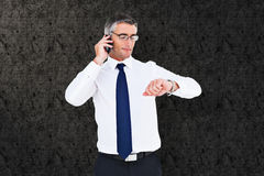 Composite image of businessman on the phone looking at his wrist watch Royalty Free Stock Image