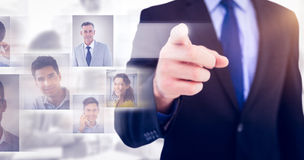 Composite image of businessman pointing his finger at camera. Businessman pointing his finger at camera against white background with vignette stock photography