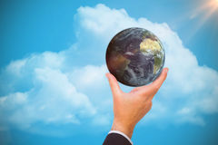 Composite image of businessman presenting earth with his finger Stock Images