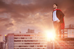 Composite image of businessman pretending to be super hero with hands on hip. Businessman pretending to be super hero with hands on hip against office buildings royalty free stock images
