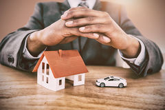 Composite image of businessman protecting house model and car with hands on table Royalty Free Stock Photo