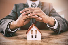 Composite image of businessman protecting house model with hands on table Stock Photo