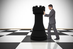Composite image of businessman pushing chess piece Stock Photography