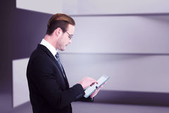 Composite image of businessman in reading glasses using his tablet pc Royalty Free Stock Photo
