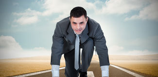 Composite image of businessman ready to race Stock Photos