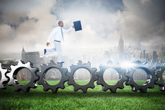 Composite image of businessman running with briefcase Royalty Free Stock Photo