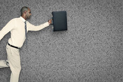 Composite image of businessman running with briefcase Stock Images