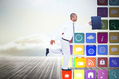 Composite image of businessman running with briefcase Stock Image