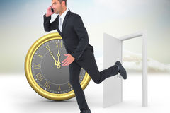 Composite image of businessman running on the phone Stock Photography